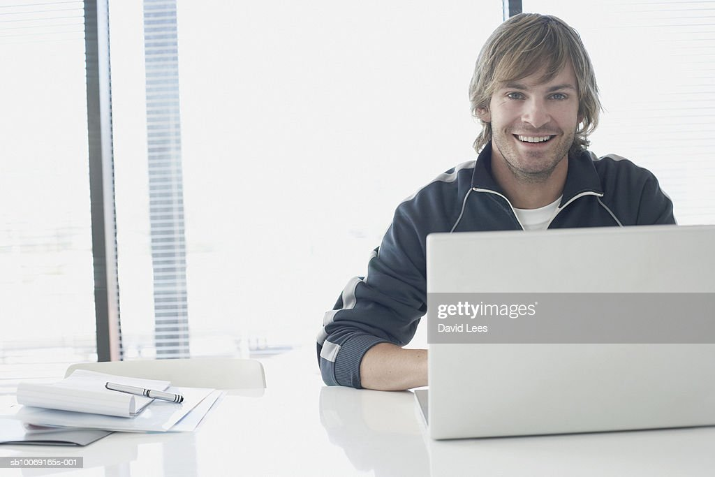 Portrait of man using laptop in office : Stockfoto