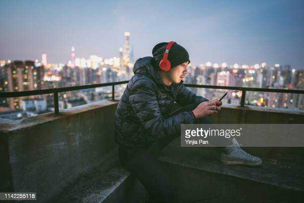 portrait of man using smartphone with headphones on rooftop - digital native stock pictures, royalty-free photos & images