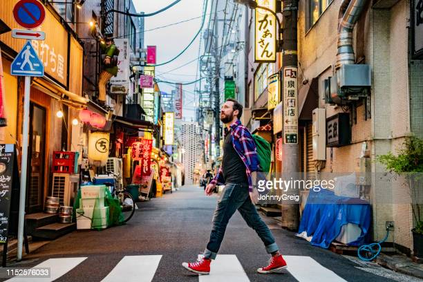 portrait of man walking on zebra crossing on tokyo street - 35 year old man stock pictures, royalty-free photos & images