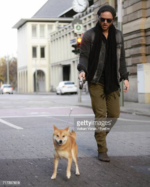 Portrait Of Man Walking With Shiba Inu On Footpath In City