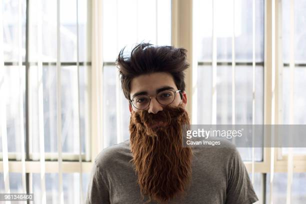 portrait of man wearing artificial mustache and beard at home - fälschung stock-fotos und bilder