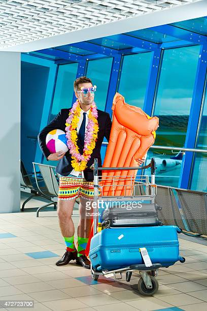 portrait of man wearing beach short and jacket at airport - practical joke stock photos and pictures