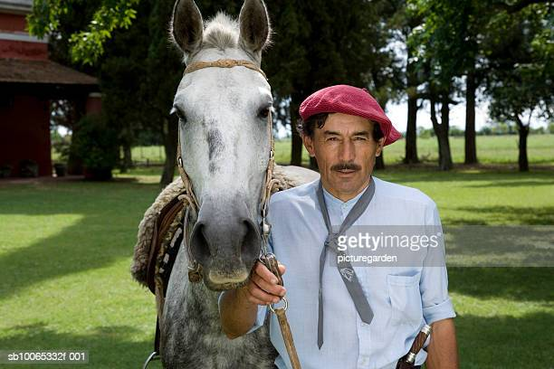 portrait of man wearing beret holding harness of horse in park - argentina traditional clothing stock photos and pictures