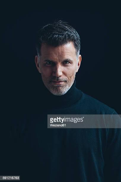 Portrait of man wearing black turtleneck in front of black background