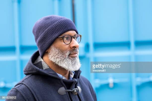 Portrait of man wearing blue woolly hat watching something