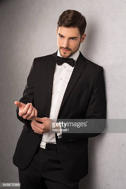 Portrait of man wearing dinner jacket and bow leaning at wall