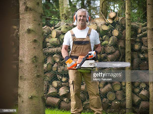 Portrait of man wearing ear protectors and visor holding chainsaw