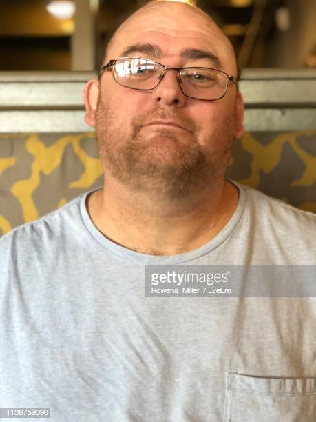 portrait of man wearing eyeglasses sitting at home - rowena miller stock photos and pictures