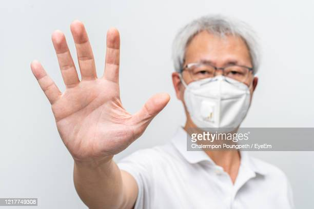 portrait of man wearing flu mask gesturing against white background - gesturing stock pictures, royalty-free photos & images