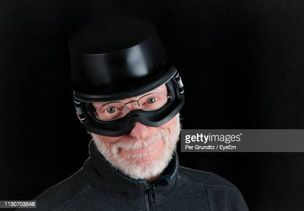 Portrait Of Man Wearing Funny Hat And Glasses Against Black Background