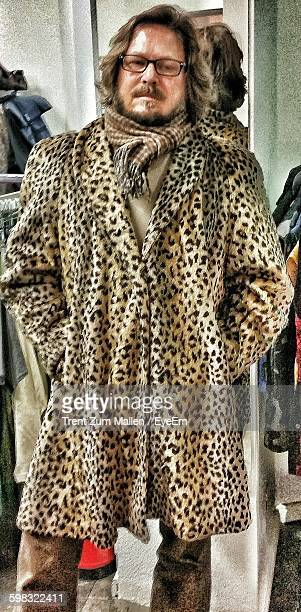 portrait of man wearing fur coat in store - overcoat stock pictures, royalty-free photos & images