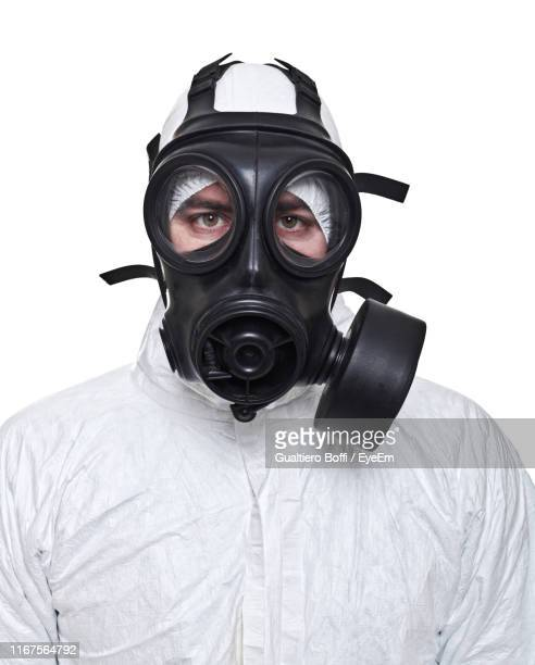 portrait of man wearing gas mask against white background - gas mask stock pictures, royalty-free photos & images