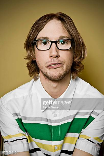 Portrait of man wearing glasses and making face, studio shot
