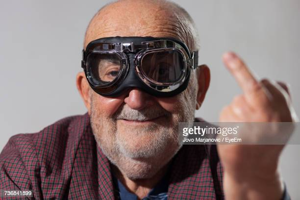 portrait of man wearing goggles - middle finger funny stock photos and pictures