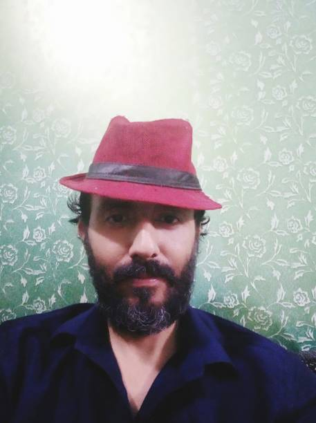 Portrait Of Man Wearing Hat Against Wall At Home