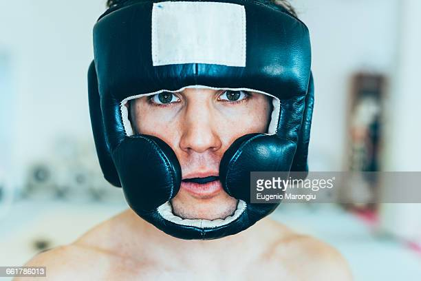 portrait of man wearing head protector looking at camera - hoofddeksel stockfoto's en -beelden