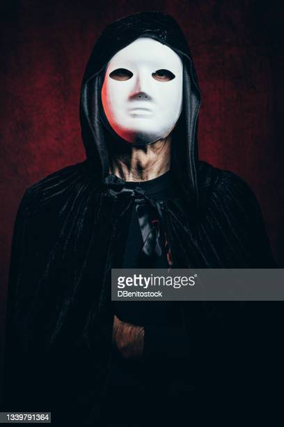 portrait of man wearing hooded cape and halloween killer mask, in dark room with victorian velvet background and red light - 13日の金曜日 ジェイソン ストックフォトと画像