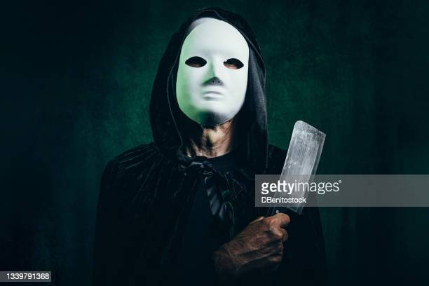portrait of man wearing hooded cape and halloween killer mask, in dark room with victorian velvet background and green light, clutching knife in menacing tone - 13日の金曜日 ジェイソン ストックフォトと画像