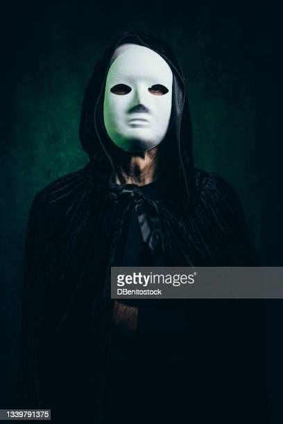 portrait of man wearing hooded cape and halloween killer mask, in dark room with victorian velvet background and green light. - 13日の金曜日 ジェイソン ストックフォトと画像