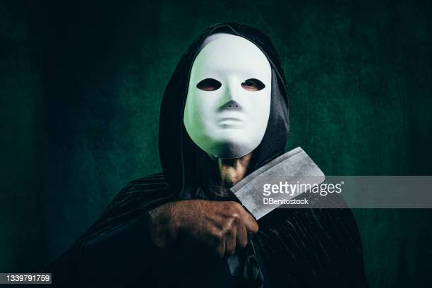 portrait of man wearing hooded cape and halloween killer mask, in dark room with victorian velvet background and green light, clutching a knife cutting his neck - 13日の金曜日 ジェイソン ストックフォトと画像