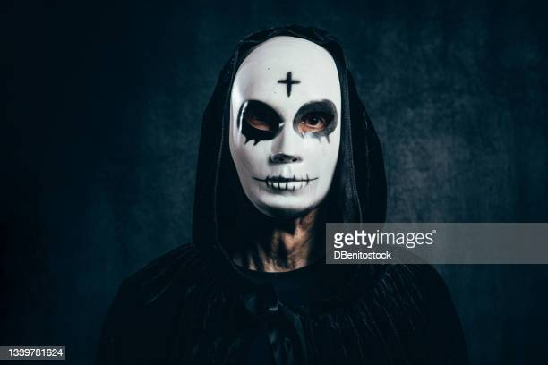 portrait of man wearing hooded cape and halloween killer mask, with cross on forehead, in dark room with velvet background and bluish light - 13日の金曜日 ジェイソン ストックフォトと画像