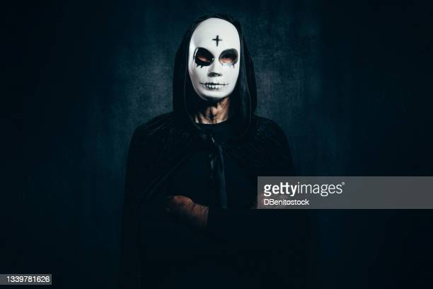portrait of man wearing hooded cape and halloween killer mask, with cross on forehead, arms crossed, in dark room with velvet background and bluish light - 13日の金曜日 ジェイソン ストックフォトと画像