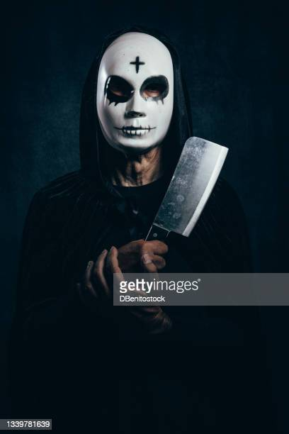 portrait of man wearing hooded cape and halloween killer mask, with cross on forehead, holding knife, in dark room with velvet background and bluish light - 13日の金曜日 ジェイソン ストックフォトと画像
