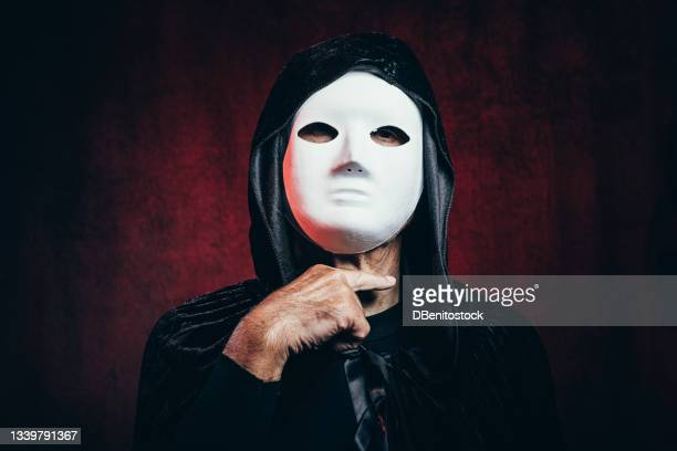 portrait of man wearing hooded cloak and halloween killer mask, in dark room with victorian velvet background and red light, making hand sign to cut neck - 13日の金曜日 ジェイソン ストックフォトと画像
