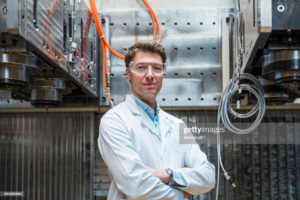 Portrait of man wearing lab coat and safety goggles at machine : Stock-Foto