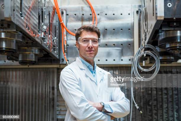 portrait of man wearing lab coat and safety goggles at machine - laborkittel stock-fotos und bilder