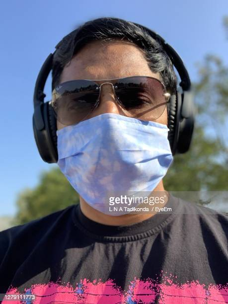 portrait of man wearing mask and headphone against blue sky - sunglasses stock pictures, royalty-free photos & images