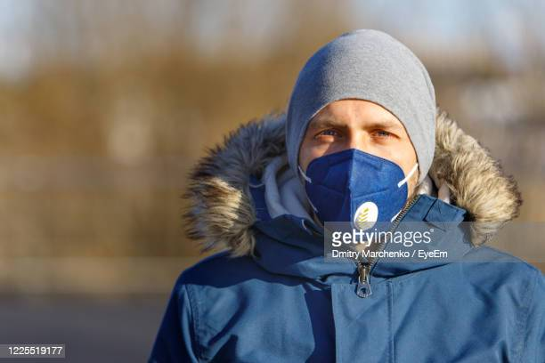 portrait of man wearing mask and warm clothing standing outdoors - coronavirus winter stock pictures, royalty-free photos & images