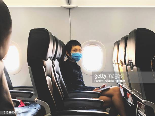 portrait of man wearing mask sitting in airplane - airplane stock pictures, royalty-free photos & images