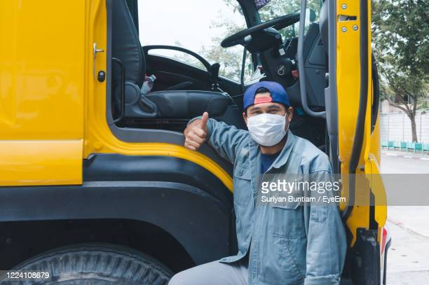 portrait of man wearing mask standing by truck - essential workers stock pictures, royalty-free photos & images