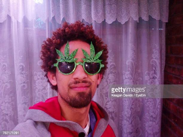 Portrait Of Man Wearing Novelty Glasses Against Curtain At Home