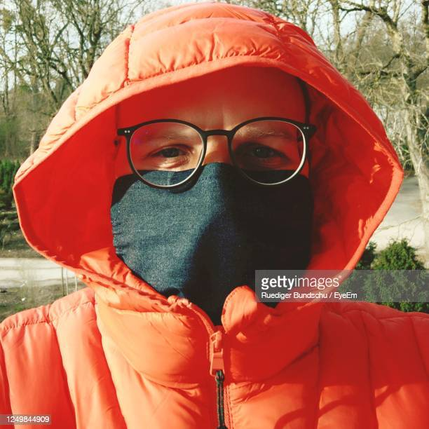 portrait of man wearing orange jacket and a community mask at the corona crisis - eyeem collection stock pictures, royalty-free photos & images
