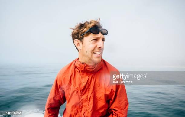 portrait of man wearing orange jacket on an inflatable dingy on the ocean. - quebra ventos imagens e fotografias de stock