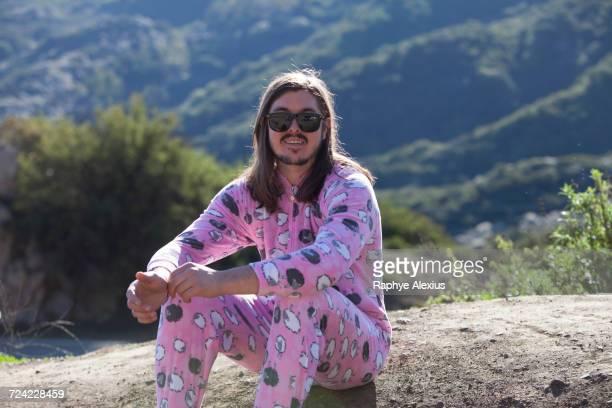 Portrait of man wearing pink onesie, Malibu Canyon, California, USA