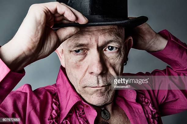 Portrait of man wearing pink shirt with frills putting on top hat