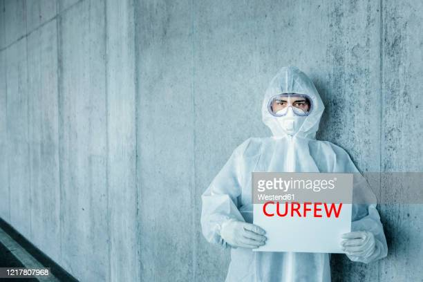 portrait of man wearing protective clothing holding a 'curfew' sign - curfew stock pictures, royalty-free photos & images