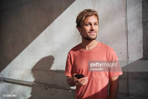 portrait of man wearing red t-shirt holding cell phone at concrete wall - männer stock-fotos und bilder