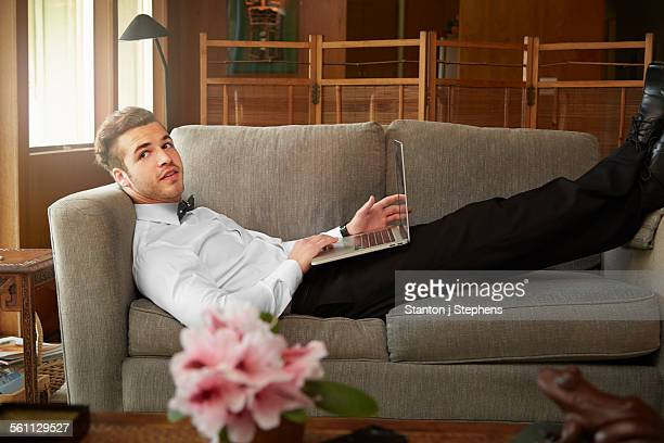 Portrait of man wearing smart clothes laying on sofa using laptop