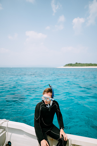 Portrait of man wearing snorkel mask and wetsuit on boat over blue tropical water, Okinawa, Japan - gettyimageskorea