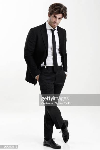 portrait of man wearing suit standing with hands in pockets against white background - pantalones negros fotografías e imágenes de stock