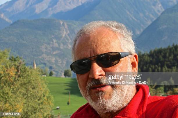 portrait of man wearing sunglasses against mountains - antonella di martino foto e immagini stock