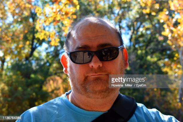 portrait of man wearing sunglasses against trees - rowena miller stock photos and pictures