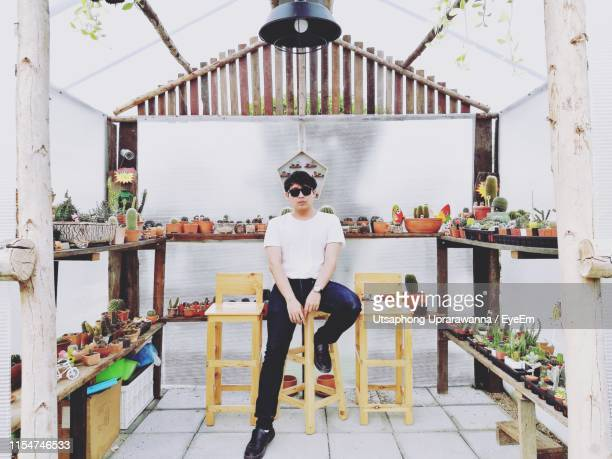 portrait of man wearing sunglasses sitting in plant nursery - eyeem collection stock pictures, royalty-free photos & images
