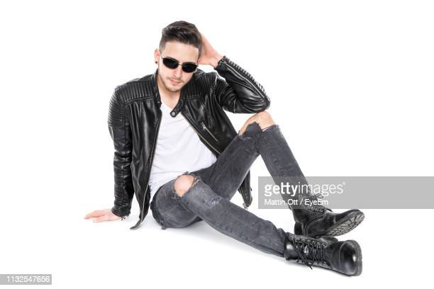 portrait of man wearing sunglasses while sitting against white background - giacca nera foto e immagini stock