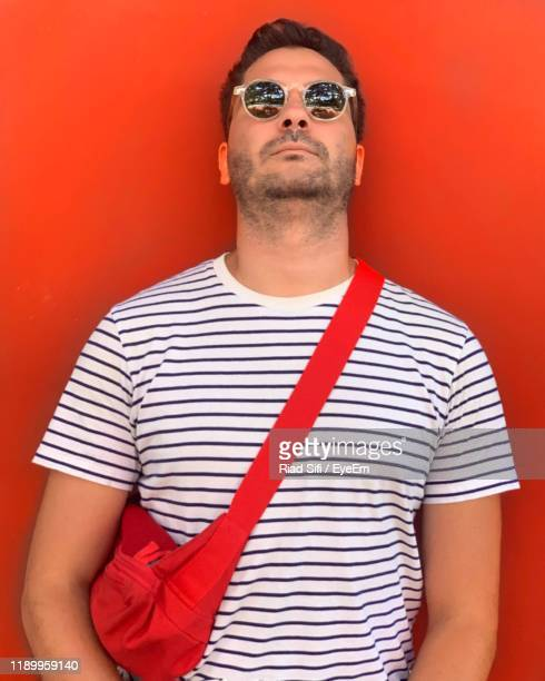 portrait of man wearing sunglasses while standing against red background - ウエストポーチ ストックフォトと画像