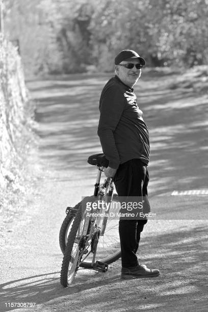 portrait of man wearing sunglasses with bicycle standing on road - antonella di martino foto e immagini stock